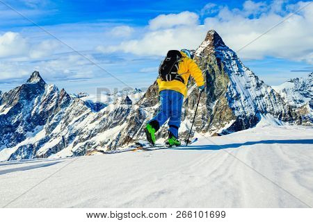 Man skiing on fresh powder snow. Ski in winter season, mountains and ski touring backcountry equipments on the top of snowy mountains in sunny day with Matterhorn in background, Zermatt in Swiss Alps.