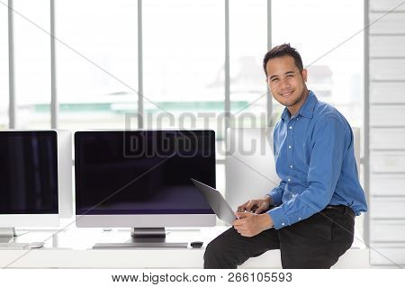 Young Asiabn Businessman Sitting And Holding New Laptop Computer With Happiness Manner In Modern Off