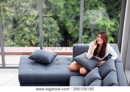 Asian Woman Sit On Sofa Use Smartphone Near Big Glass Windows, Relaxing Alone In House With Green Fo