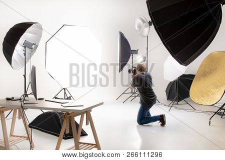 Photographer  Working In Modern Lighting Studio With Many Kinds Of Flash And Accessories. Taking To