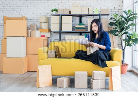 Young And Beautiful Asian Woman Sitting Among Several Boxes And Checking Parcels On The Yellow Sofa,