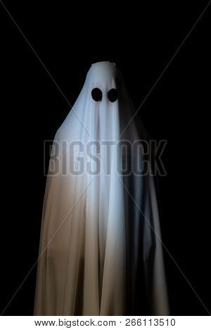 Someone Covered With White Cloth With Big Black Eyes On Black Background Look Like Ghost In Night. C