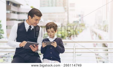 Father And Son Playing Game Smart Phone Together On Business District Urban, Dad And Son Happy Famil