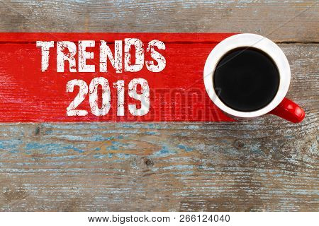 Trends 2019 / Cup Of Coffee With Trends Inscription On Wooden Background.