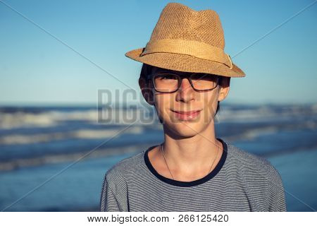 Young boy posing in hat at the summer beach. Cute spectacled smiling happy 12 years old boy at seaside, looking at camera. Kid's outdoor portrait over seaside, fashion hipster style.