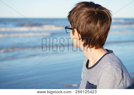Young boy posing at the summer beach. Cute spectacled 12 years old boy at seaside, looking at sea. Kid's outdoor portrait over seaside.