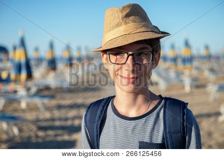 Young boy in hat and glasses posing at the summer beach. Cute smiling happy 12 years old boy at seaside, looking at camera. Kid's outdoor portrait over seaside.