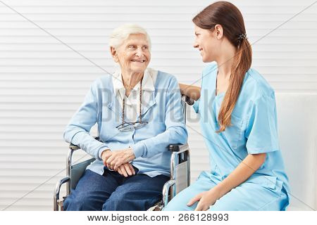 Frail senior woman in wheelchair with nursing wife at nursing