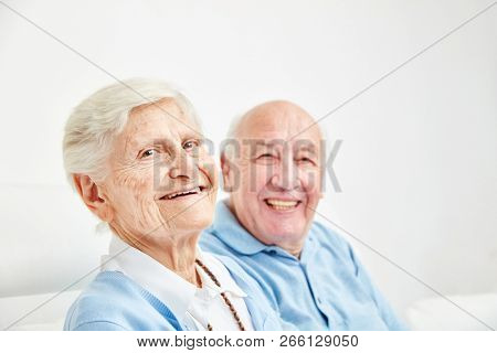 Happy retired couple sitting on the sofa at home or in retirement home