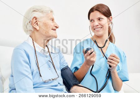 Young caregiver makes a blood pressure measurement at senior woman as a precaution at home