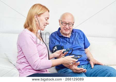 Young woman with blood pressure monitor controls the blood pressure in a senior