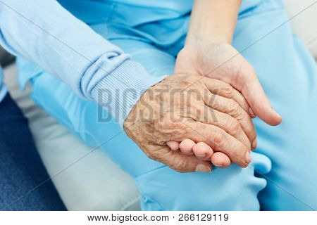 Nursing or caring nurse holds a senior's hand as a consolation
