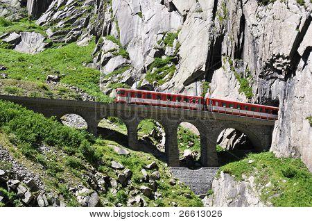 Alpine express passing bridge at St. Gotthard Pass in Switzerland