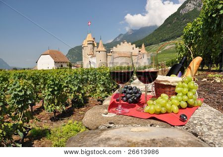 Red wine and grapes against Chateau d'Aigle castle. Switzerland poster