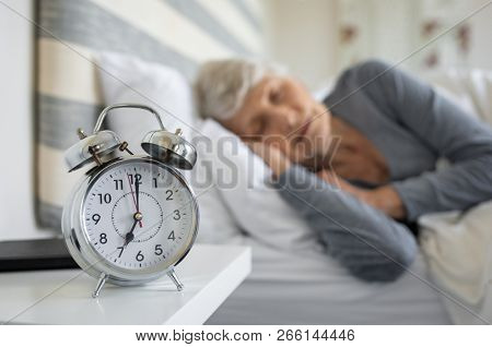 Closeup of alarm clock with senior woman in deep sleep at home. Old woman sleeping in bed next to alarm clock in morning. Elderly woman sleeping in bedroom peacefully.
