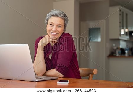 Beautiful senior woman using laptop at home. Mature smiling woman looking at camera while working with computer. Portrait of happy modern retired lady with laptop sitting on living room.