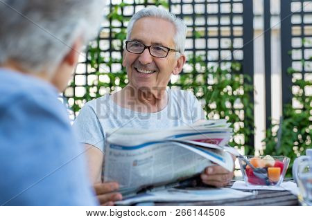 Senior couple reading newspaper during breakfast. Portrait of happy old man with grey hair reading the news with wife in the morning. Elderly couple discussing while reading newspaper outdoor.