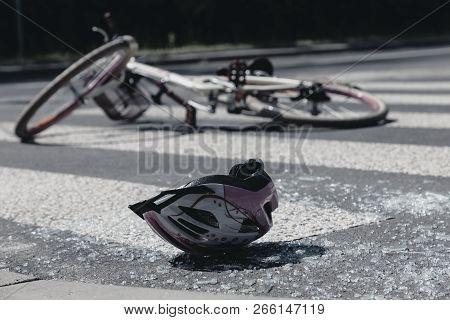 Broken child's helmet and bike on pedestrian crossing after terrible accident poster