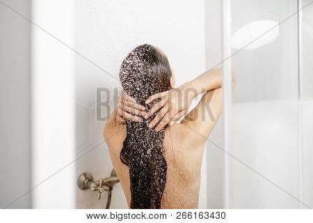 Woman Washing Her Beautiful Long Hair, While Taking A Shower Standing Back In The Shower Cabin