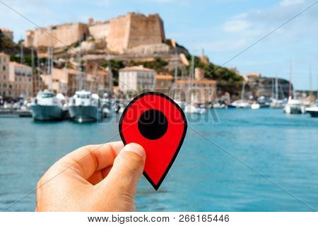 closeup of the hand of a caucasian man holding a red marker at the port of Bonifacio, in Corse, France, and its famous citadel in the background