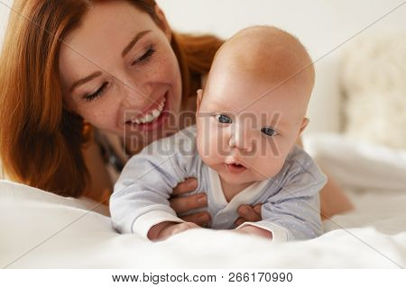 Picture Of Cheerful Beautiful Young Red Haired Caucasian Mother Holding Her Adorable Infant Child Wh