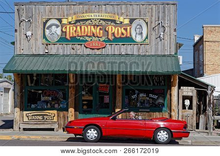 Custer, South Dakota, September 16, 2018 : Red Car And Old Trading Post In Custer. A Trading Post Wa