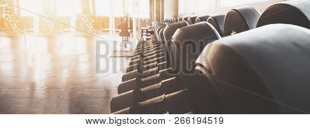 Gym Equipment Wide Interior Gym For Fitness Banner Background Close Up Dumbbells And Blurred Equipme