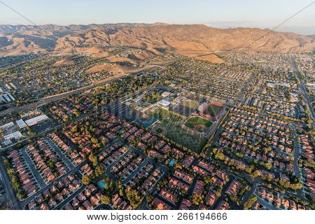 Aerial view of modern suburban housing, the 118 freeway and Rocky Peak Mountain Park near Los Angeles in Simi Valley, California.