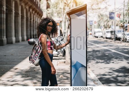 Dazzling Curly Hipster Girl Is Completing Her Payment Via Electronic Street Parking Kiosk; A Charmin