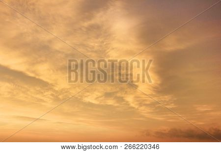 Sunset Sky Background With Soft Orange, Yellow And Blue Sky Colors. Scenic Sky Cloudscape At Sunset