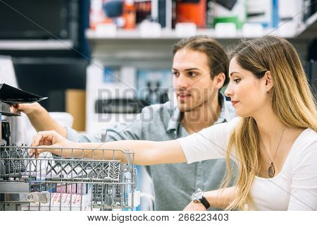 Close Up Of A Young Couple Of Costumers Are Choosing A Dishwasher In An Appliances Store. Cyber Mond