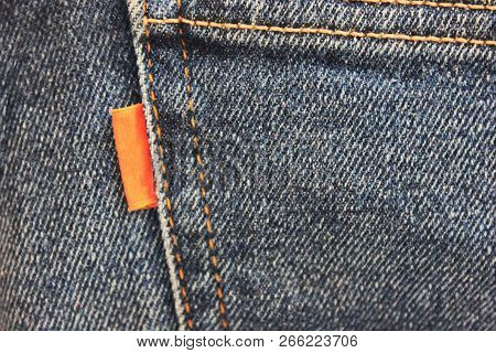 Dark Denim Blue Jeans With Empty Red Label Close Up Top View. Casual Vintage Style Jean Clothing Bac