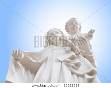 Madonna and Jesus child - from below white statue of holy Virgin Mary mother of the child Jesus on background of blue sky