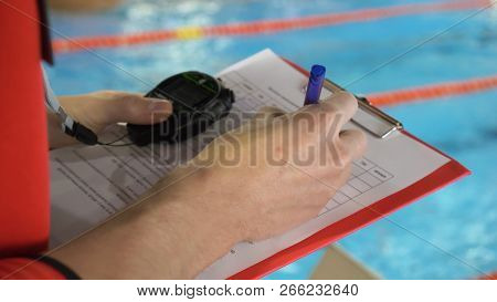 Judge At Competition In Pool. Close-up Of The Judge's Hand In The Pool Which Records The Testimony I
