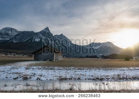 Winter Alpine Landscape With A Wooden Cabin, A Frozen River And The Snowy Alps Mountains At Sunset,