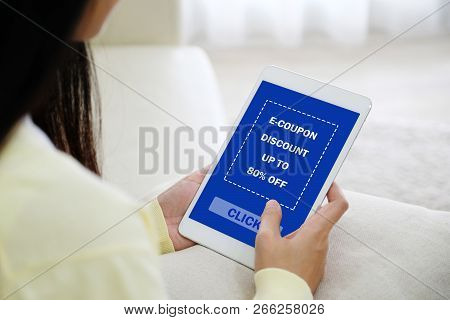 Woman Hand Typing Discount Coupon Code On Digital Tablet Screen To Get The Shopping Online Promotion