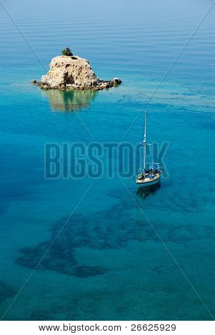 Aerial view of a sailing boat in transparent water of sea with a small island solitary