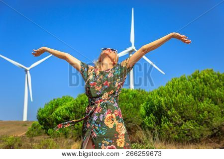 A Blond Happy Woman With Open Arms With Wind Turbines Rotating In Sagres, Algarve, Portugal. Alterna