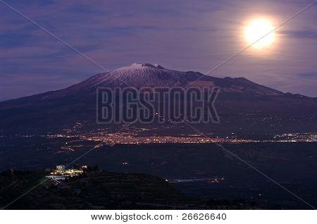 moonlight on the volcano Etna and night skyline of Adrano from Centuripe, Italy