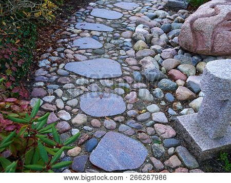Classical Design Walkway Path Made Of Different Size Stones Through A Garden