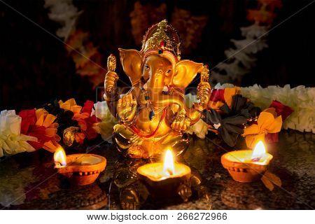 Ganesh Chaturthi or Diwali concept - Ganesha  figurine with Diwali lights oil ghee candles,  India