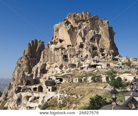 the Uchisar castle is a tall vulcanic rock outcrop riddled with tunnels and windows visible for miles around in Cappadocia, Turkey
