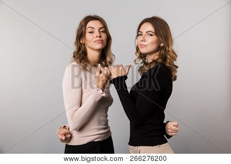 Image of two beautiful women smiling and hooking each others little fingers in conciliation or friendship isolated over gray background