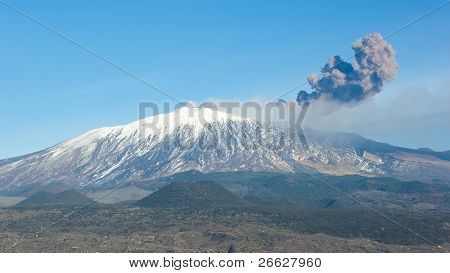 from one side of the volcano Etna rises a tall column of smoke - eruption of 12 genuary 2011 - cooled lava (sciara) flows out