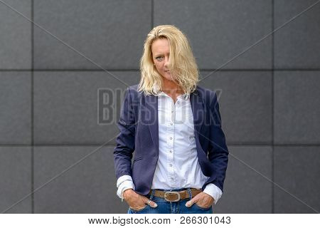 Attractive Serious Trendy Blond Woman Standing With Hands In Pockets And Hair Falling In Front Of He