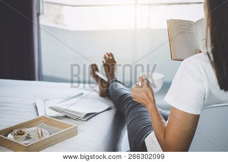 Young Woman Happiness On Bedroom In Enjoying Reading Book And Newspaper In Holiday With Morning Coff