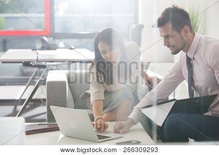 Two young business people working on proposal in a casual creative environment