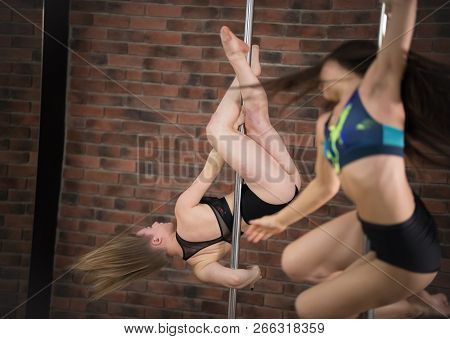Two Girls Training Pole Dance In A Studio. Spinning On The Pole