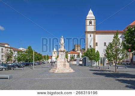 Dom Pedro V square with Dom Pedro V statue and Igreja de Santa Maria da Devesa Church and castle in the back. Castelo de Vide, Alto Alentejo, Portugal