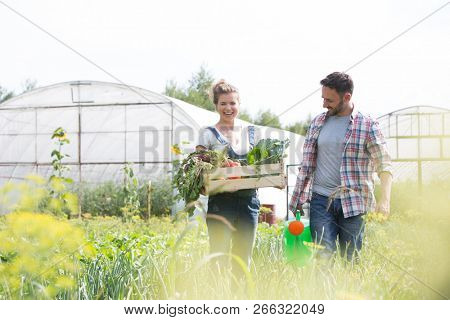 Farmer holding organic produce in wooden box on her farm with gardener holding watering can next to her